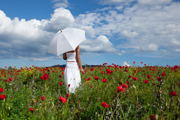 Woman with white umbrella standing in field of red poppies