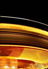 Rotating fairground ride at night
