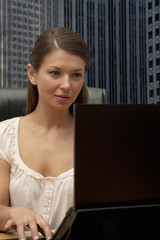Businesswoman working at desk in office and using laptop
