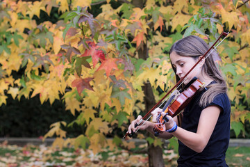 Girl playing violin with autumn foliage in background