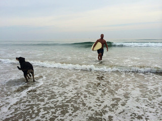Man coming out of sea with surfboard