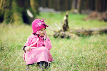 Little girl (2-3) sitting in forest