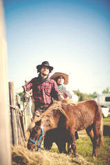 Cowboy and cowgirl couple with pony