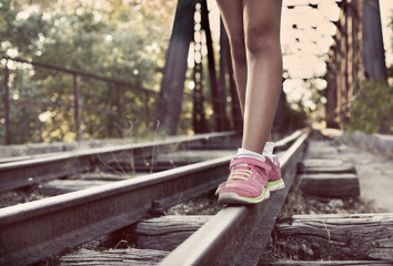 Spain, Girl walking along train tracks
