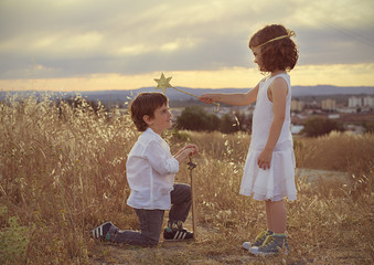 Boy (4-5) kneeling down in front of girl (6-7)
