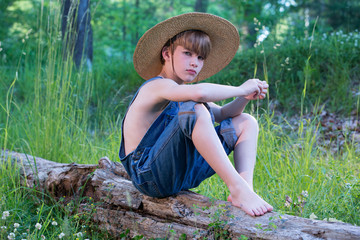 Young boy sitting on log wearing straw hat and blue overalls