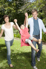 Mother and father playing with child, swinging daughter between them