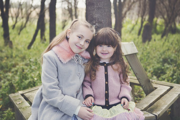 Portrait of sisters sitting on bench