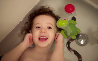 Toddler girl (2-3) with curly hair in bath