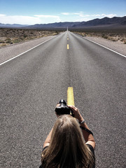 USA, California, Woman taking photograph of infinity road