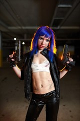 Sexy woman with blue hair holding two guns and looking as killer