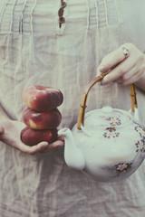 United Kingdom, England, Warwickshire, Stratford-upon-Avon, Woman holding peaches and oriental tea pot