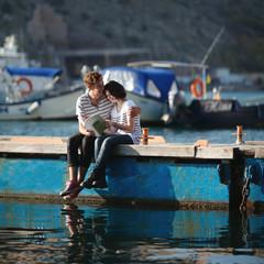 Teenage couple (14-15) sitting on jetty, embracing