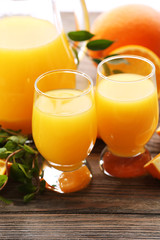 Glass of orange juice and slices on wooden table background