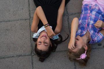 Kids (6-7, 8-9) laying on pavement and laughing