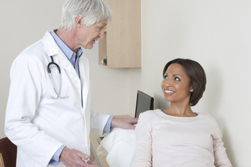 Doctor talking to female patient in examination room