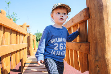 Boy (2-3) standing on bridge
