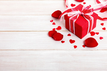 Valentine background of gift box and rose petals on white wood.