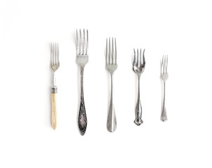 A set of vintage dinnerware: forks of different shapes and sizes
