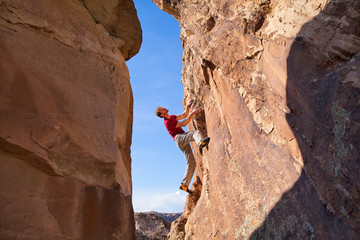USA, Colorado, Man climbing on boulder