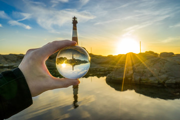 Norway, Rogaland, Eigeroy lighthouse and sunset seen through crystal ball