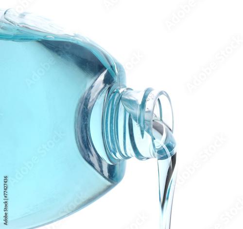 Leinwandbild Motiv Cosmetic liquid pouring from bottle isolated on white