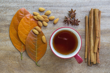 Still life of autumn leaves, almond seeds, cup of tea, anise cloves, and cinnamon sticks on wooden surface