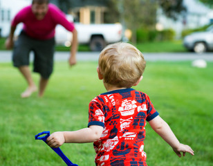 USA, Indiana, Little boy running to dad outside on a summer night