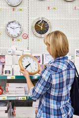 Woman chooses wall clock in store
