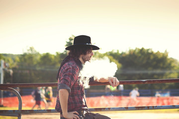 Cowboy leaning on fence and exhaling smoke