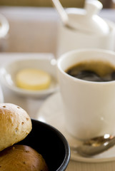 Bread rolls with butter and black coffee on table