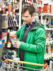 Man buying handsaw in store