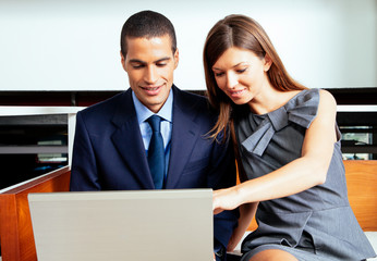 Businessman and businesswoman looking at a laptop in the office