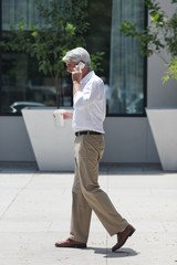 Side view of businessman walking down street while talking on mobile phone