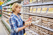 Woman chooses packing eggs in supermarket - 77428840