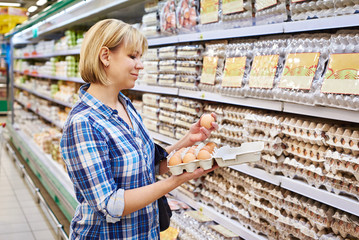Woman chooses packing eggs in supermarket