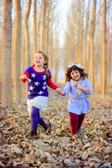Two girls in park holding hands and running in dry leaves