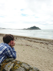 United Kingdom, Cornwall, Marazion, Boy lying on rock and looking at view