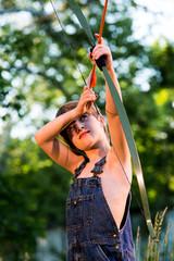 Young boy aiming arrow