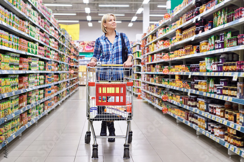 Women with cart shopping in supermarket - 77429690