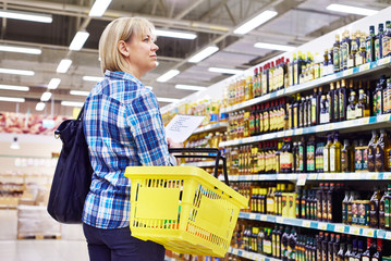 Woman housewife with list shopping in department store plant oil