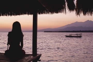 Indonesia, West Nusa Tenggara, Mataram, Ampenan, Pulau Meno, Young woman watching sunrise on sea with volcano Rinjani volcano in background