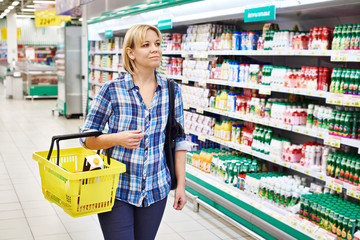 Women housewife with yellow basket shopping in dairy department
