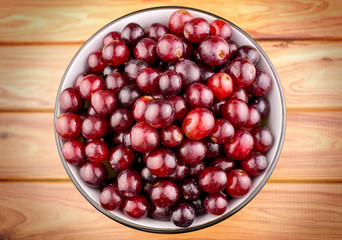 Juicy red grapes in bowl on wooden background