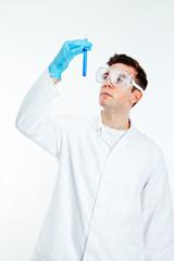 Scientist looking at test tube of blue liquid