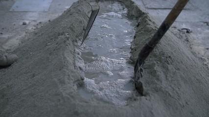Men enlarging hole full of water