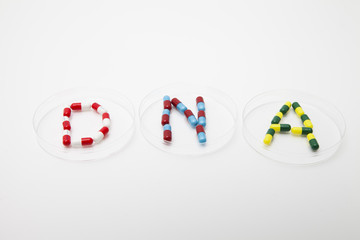 DNA word made up of pills in petri dish