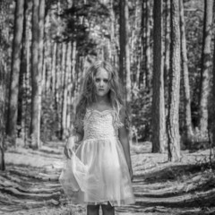 Portrait of sad girl (4-5) in forest