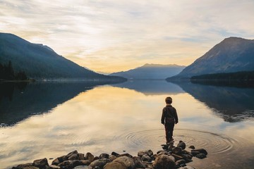 Boy (4-5) standing at water's edge looking at view