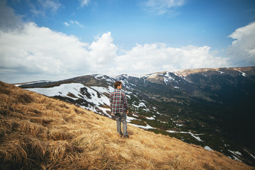 Young man standing in field and looking at view